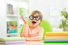 Портрет ухищренной девушки ребенк с книгами крытыми Стоковое Фото