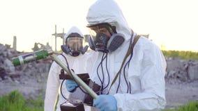 Портрет 2 ученых в белых прозодеждах и защитных масках принимая измерения радиации на заход солнца на видеоматериал