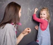 Портрет учителя и маленьких студента, матери и дочери около классн классного Стоковое Фото