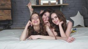 Портрет лучших другов девушки лежа на кровати усмехаясь и смотря камеру движение медленное сток-видео