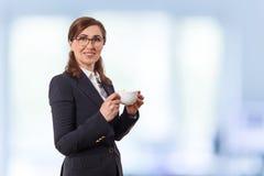Портрет ушей красивых коммерсантки 50 старых с чашкой кофе в офисе Стоковое Фото