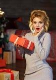 Портрет удивленной белокурой девушки очарования с подарками в руках дальше Стоковые Изображения RF