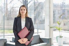 Портрет файла удерживания коммерсантки пока стоящ на лобби офиса Стоковые Фотографии RF