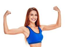 Портрет фитнеса женщины усмехаясь показывать бицепс на руках Стоковые Фотографии RF