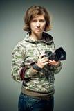 портрет фотографа держа превосходную ретро камеру в ее нежных руках Брюнет смотрит вверх с лукавым взглядом и серьезным p стоковые изображения