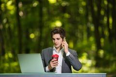 Портрет фрилансера сидя на работе стола офиса на мобильном телефоне портативного компьютера и чашки кофе говоря на дороге зеленог Стоковая Фотография RF
