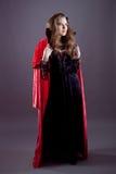 Молодые женщины в красном длиннем плаще Стоковое фото RF
