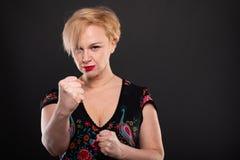Портрет холодной модной женщины представляя показывающ кулаки стоковое изображение rf