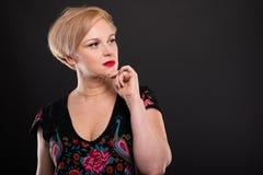 Портрет холодной модной женщины представляя с рукой на подбородке стоковое фото