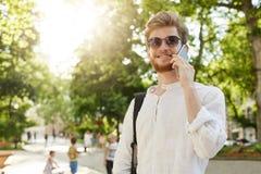 Портрет хорошего смотрящ красного с волосами человека в белых рубашке и солнечных очках усмехаясь, говоря на телефоне на пути на  Стоковые Изображения