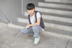 Портрет холодного азиатского ребенк представляя outdoors Стоковое Изображение