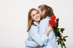 Портрет цветков привлекательных молодого человека пряча от его изолированной подруги перед давать ей сюрприз над белизной Стоковое фото RF