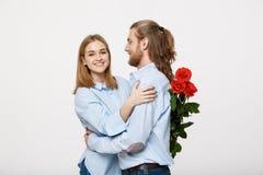 Портрет цветков привлекательных молодого человека пряча от его изолированной подруги перед давать ей сюрприз над белизной Стоковые Изображения RF