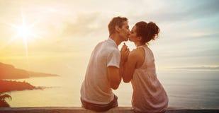 Портрет целуя watchnig пар заход солнца Стоковая Фотография