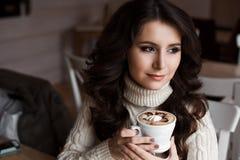 Портрет чая и смотреть молодой шикарной женщины выпивая заботливо вне окно кафа, наслаждаясь ее отдыхом Стоковые Изображения RF