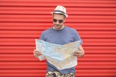 Портрет человека битника держа карту изолированный на красной стене металла перемещение карты dublin принципиальной схемы города  стоковая фотография