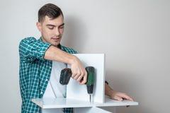 Портрет человека в случайных одеждах в электрической отвертке собирает рабочий стол с экземпляром космоса стоковые фотографии rf