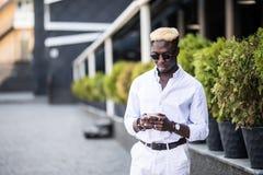 Портрет человека жизнерадостного стильного молодого Афро американского используя свободный город Wi-Fi пока беседующ с друзьями ч стоковые фото