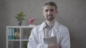 Портрет человека красивого навыка усмехаясь в белой робе смотря в планшете удерживания камеры Взрослый доктор в современном сток-видео