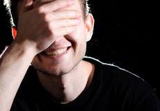 Портрет человека на черной предпосылке, усмехающся при красивая улыбка, покрывая его наблюдает с его рукой, белыми зубами стоковое фото