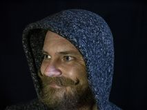 Портрет человека с бородой и усика в клобуке с усмехаясь стороной на черной предпосылке стоковое изображение rf