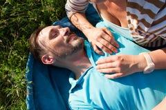 Портрет человека с руками женщины на его человеке комода усмехаясь кладя на голубое одеяло и зеленую траву с руками подруги стоковые изображения