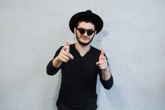 Портрет человека хипстера одетый в черноте, с солнечными очками и шляпой, указывая пальцы на камеру на белой предпосылке да стоковое изображение
