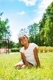 Портрет черной девушки в парке мечтая на лужайке Стоковое Изображение RF