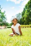 Портрет черной девушки в парке сидя на лужайке Стоковые Изображения