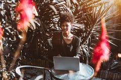 Портрет черной курчавой девушки в парке с компьтер-книжкой Стоковые Изображения RF