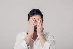 Портрет человека в белой рубашке закрывает его глаза с руками стоковые фото