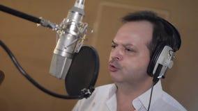 Портрет человека в белой рубашке поет в наушниках перед микрофоном студия акции видеоматериалы