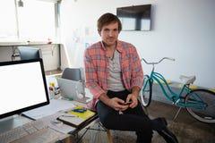 Портрет человека используя телефон пока сидящ на столе на офисе Стоковое Фото