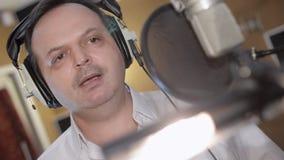 Портрет человека поет в наушниках перед микрофоном студия Движение головы акции видеоматериалы