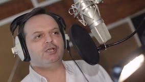 Портрет человека поет в наушниках перед микрофоном студия gesture сток-видео