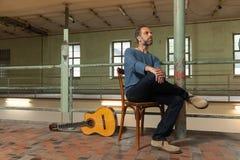 Портрет человека с гитарой, промышленным положением Стоковые Изображения