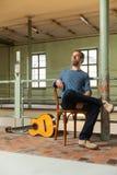 Портрет человека с гитарой, промышленным положением Стоковое Изображение RF