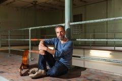 Портрет человека с гитарой, промышленным положением Стоковое фото RF