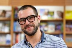 Портрет человека с стеклами в bookstore Стоковая Фотография
