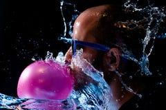 Портрет человека с стеклами солнца жевательной резиной и быть брошенной водой в стороне Стоковые Фотографии RF