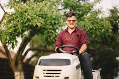 Портрет человека lawncare задворк - усмехаясь работник используя езду на косилке травы Стоковое фото RF