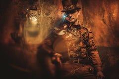 Портрет человека steampunk с различными механическими приспособлениями на винтажной предпосылке steampunk Стоковая Фотография