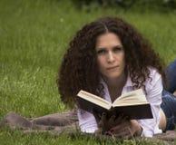 Портрет чтения outdoors счастливого студента расслабленного Стоковые Фото