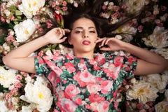 Портрет чувственной женщины лежа вниз на цветках Стоковое фото RF