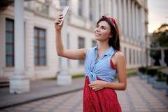 Портрет чудесной кавказской женщины принимая selfie с smartphone в Европе Битник брюнет женский с прошивкой внутри Стоковая Фотография