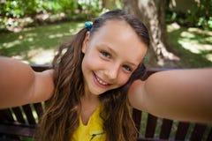Портрет шаловливой девушки сидя на стенде Стоковое Изображение