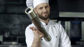 Портрет шеф-повара мужской на ресторане кухни Мужской шеф-повар играя с перечницей сток-видео