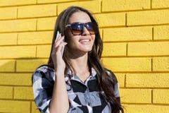 Портрет шикарной женщины используя мобильный телефон перед yello Стоковые Фотографии RF