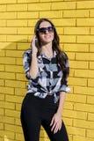 Портрет шикарной женщины используя мобильный телефон перед yello Стоковые Фото