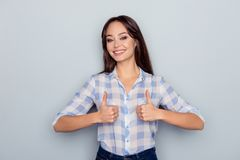 Портрет шикарной, милой, жизнерадостной женщины показывая 2 большого пальца руки вверх Стоковые Изображения